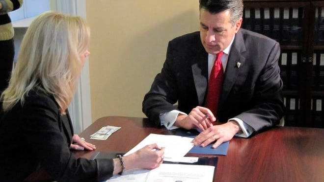 Gov. Brian Sandoval fills out paperwork with elections officer Shelly Capurro in Carson City, Nev. on Friday, March 7, 2014, to launch his re-election bid. Sandoval, a first-term Republican, said he plans an aggressive campaign and is committed to serving out a full term if re-elected in November. (AP Photo/Sandra Chereb)