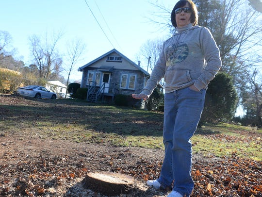 Kris Garrison stands by the stump of a blue spruce