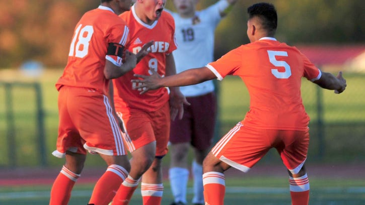 Seniors Leandro Suarez and Armando Caamano celebrate Dover's tying goal with sophomore Isaiah Flores, who scored.