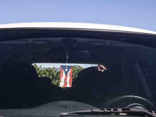 Pablo Robles, puts his guitar in his car after the