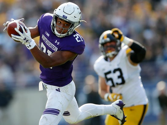 Northwestern's Justin Jackson makes a catch in front of Iowa's Will Anthony during the second half Oct. 21, 2017 in Evanston, Ill.