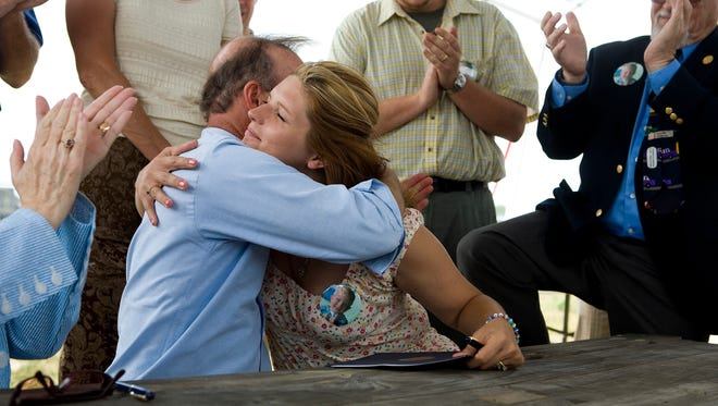 BENJAMIN REED / Courier & Press ARCHIVESGovernor Mitch Daniels hugs Kathryn Martin, mother of 2-year-old C.J. Martin, who was killed in the tornado of Nov. 6, 2005. Governor Daniels completed the signing of C.J.'s Law Thursday, requiring licensed mobile-home installers to supply weather alert radios that warn residents of severe weather.