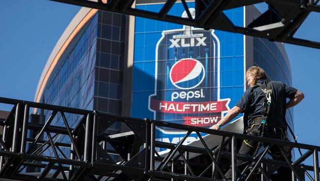 A contract employee of NRG Stadium sets up a band stage in downtown Phoenix getting ready for Super Bowl XLIX this past February. Ad spots for Super Bowl 50 are already hitting record levels ahead of the 2016 game.