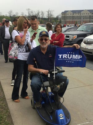Ron Formosa holds a Donald Trump flag Thursday evening during a political rally in Harrisburg.