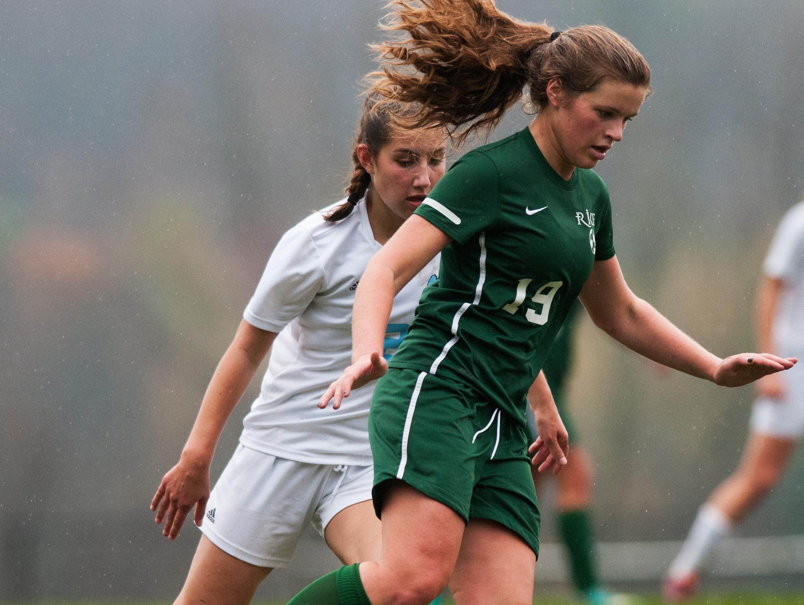 Rice's Margot Rathke (19) runs with the ball past MMU's Amelia Knakal (2) during the girls soccer playoff game between the Rice Green Knights and the Mount Mansfield Cougars at MMU in 2014.