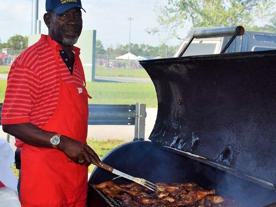 Dan Aaron prepares barbecue chicken at the veterans'