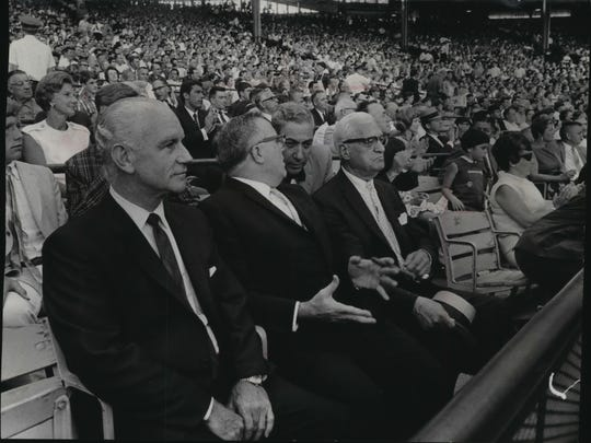 Three of baseball's top executives watch the exhibition