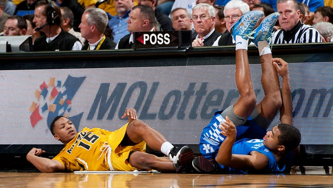 Missouri's Wes Clark, left, lies on the court next to Kentucky's Aaron Harrison, right, after Clark collided with Harrison while chasing a loose ball during the second half of an NCAA college basketball game Thursday, Jan. 29, 2015, in Columbia, Mo. Kentucky won 69-53. (AP Photo/L.G. Patterson)