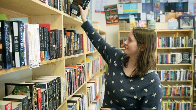 Kate Larson, store manager at Liberty Bay Books in Bremerton, puts away books Thursday. The store is participating in Saturday's Independent Bookstore Day.