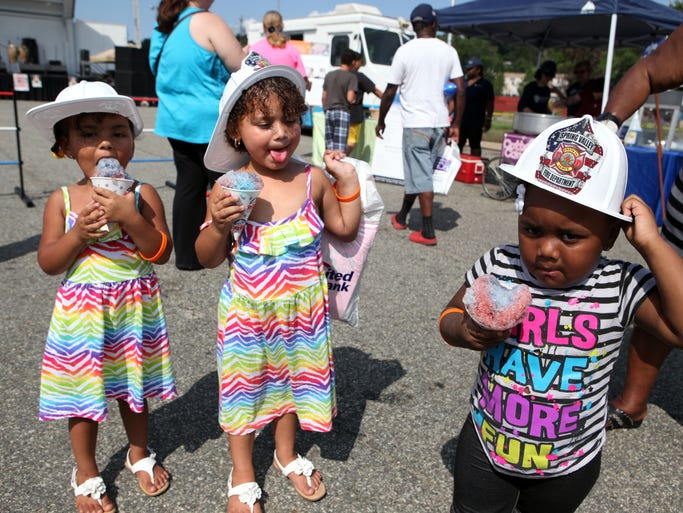 Kira Vaughan, 3, left, Tiauna Vaughan, 4, and Zariah Price, 2, eat snow cones at the 11th annual Spring Valley Day, Aug. 10, 2014 in Memorial Park. The event included Zumba classes, face painting, entertainment, educational vendors and other fun-filled activities.