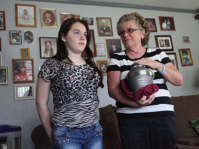 Christine Eby holds the urn containing the remains of 35 year-old son Daniel who died from a speed ball made with cocaine and heroin Oct. 4, 2013 in the bathroom of her home. Daniel's 10 year-old daughter Danielle stands with her grandmother who has been taking care of her on and off since she was 3 years-old, Friday, May 30, 2014.