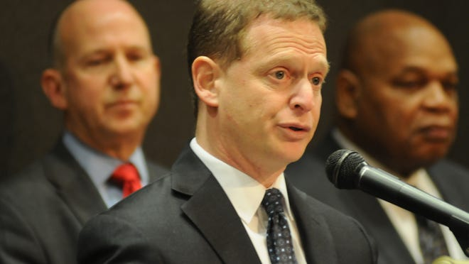 Delaware Attorney General Matt Denn (center) outlines a plan at a press conference Wednesday in Wilmington to spend millions from the financial crisis settlement on several initiatives including substance abuse, school and community policing among others. Gov. Jack Markell (left) and Wilmington City Council President Theo Gregory listen.