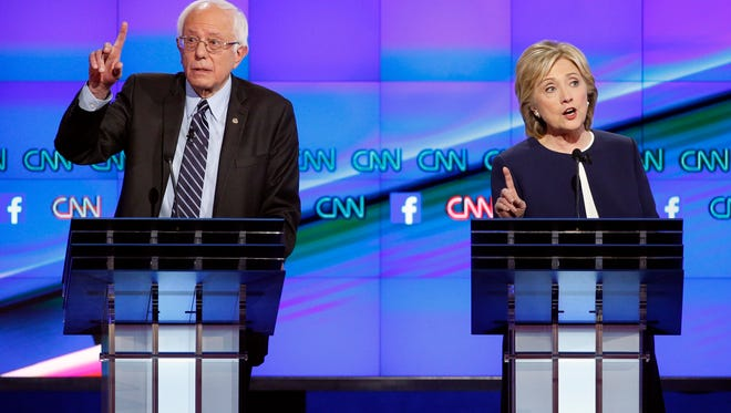 Hillary Rodham Clinton, right, and Sen. Bernie Sanders, of Vermont, speak during the CNN Democratic presidential debate on Tuesday in  Las Vegas.