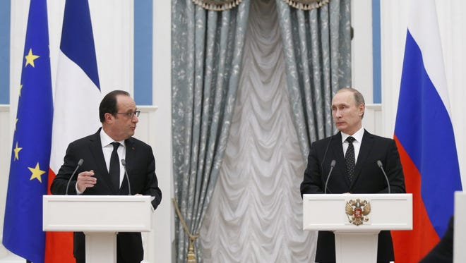 French President Francois Hollande, left, speaks during a joint press conference with his Russian counterpart Vladimir Putin after their meeting in Moscow on Nov. 26.