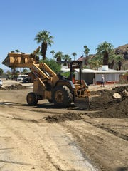 Crews clear the road at Safari Park mobile home community in Palm Springs. A rush of water left damage during Saturday's rainstorm that dropped more than an inch on the city.