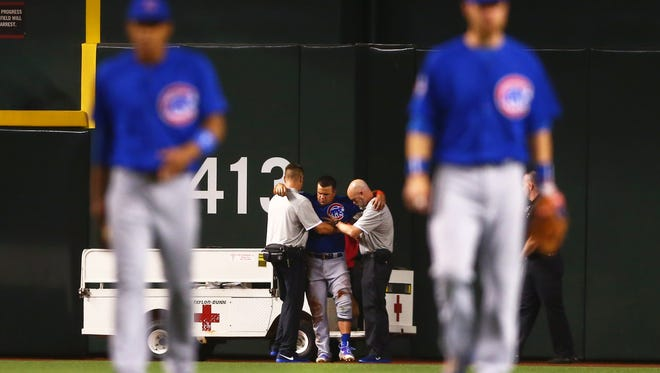 Kyle Schwarber is attended to by trainers after an outfield collision resulted in a torn ACL.
