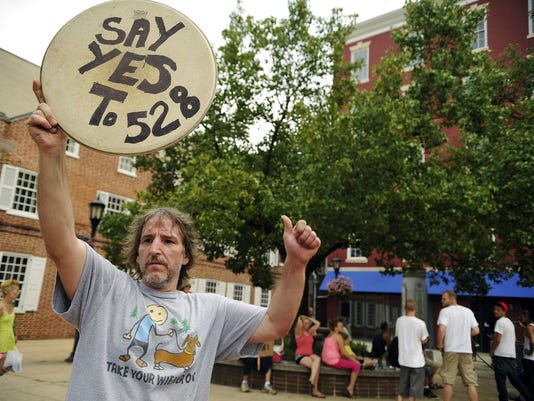 John Wise of Hellam Township holds up a drumhead sign and gives a thumbs-up to a passing motorist on West Market Street during the York Hemp Freedom Rally on Saturday, July 27, 2013, at Continental Square. About 100 people gathered in Continental Square for the York Hemp Freedom Rally on Saturday, July 27, 2013.