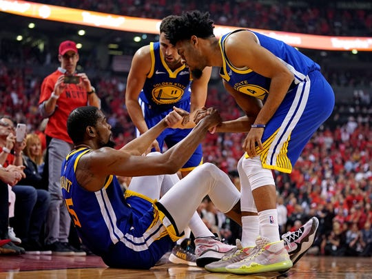 Jun 10, 2019; Toronto, Ontario, CAN; Golden State Warriors forward Kevin Durant (35) is helped up by guard Quinn Cook (4) and guard Klay Thompson (11) after an apparent injury during the second quarter in game five of the 2019 NBA Finals against the Toronto Raptors at Scotiabank Arena. Mandatory Credit: Kyle Terada-USA TODAY Sports
