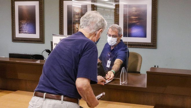 Library associate Mark Palomba helps a member check out books behind a plexiglass shield inside Palm Beach County's main library branch which reopened Monday after being shut down in response to the coronavirus, June 1, 2020.