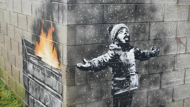 In this file photo dated Dec, 20, 2018, showing an artwork by Banksy on the side of a garage depicts a child dressed for snow playing in the falling ash and smoke from a skip fire, in Port Talbot, Wales.