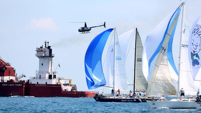 A helicopter with a photographer taking pictures and a freighter pass by sail boats about to race in start 9 of the PHRF E Division 3 Shore Course during the 2014 Bell's Beer Bayview Mackinac Race on Saturday, July 12, 2014