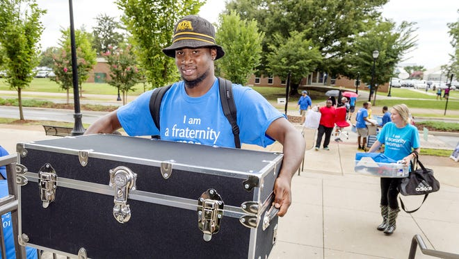 MTSU student and We-Haul move-in volunteer Ricdarius Dickerson carries a student's trunk at Cummings Hall Aug. 19.
