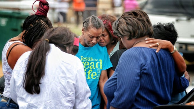 Family members gather outside the scene of a fatal house fire Monday, Sept. 12, 2016, that killed nine people, including five children.