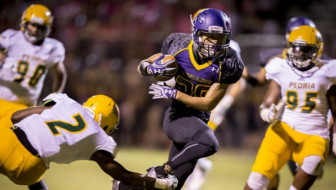 Running back Garret Veldhuizen (20) of Sunrise Mountain is tripped up by defensive back Isaiah Veal (2) of Peoria in the first half of the high school football game between Peoria and Sunrise Mountain at Sunrise Mountain High School on Thursday, October 13, 2016 in Peoria.