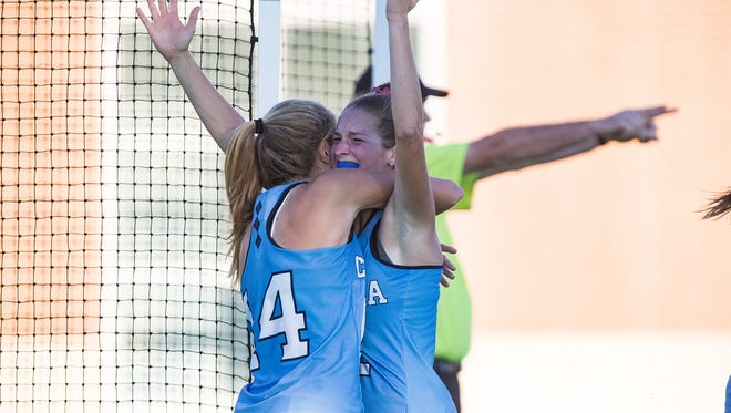 Lauren Moyer, right, lifts her hands in celebration as  teammate Emma Bozek (14) embraces her.