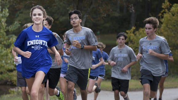 St. Joseph's sophomore Ava Dobson, who has the fastest time among girls in the state, runs with teammates in Cleveland Park on Wednesday. LAUREN PETRACCA/Staff