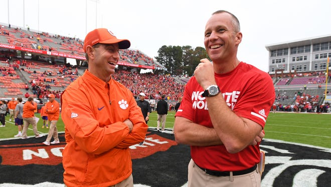 Clemson head coach Dabo Swinney and NC State head coach Dave Doeren talk at midfield during pre-game on Saturday, November 4, 2017 at N.C. State's Carter Finley Stadium in Raleigh, N.C.