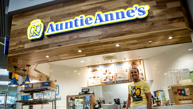 Marry Harrington poses for a picture in front of her Auntie Anne's Pretzels franchise at Indian Mound Mall.