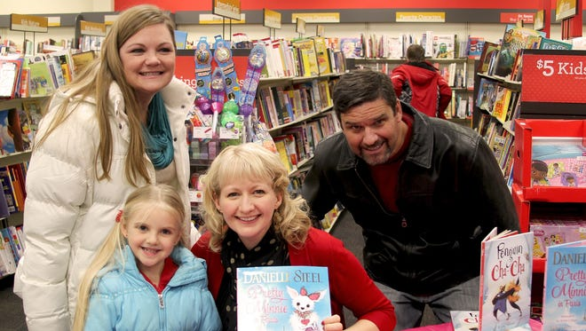 """Jennifer and Eric Serrano, back row, and their daughter, Adrianna, front left, pose with Kristi Valiant holding a copy of """"Pretty Minnie in Paris,"""" a book which she recently illustrated. The Dec. 21 book signing was hosted by Books-A-Million in the Forest Mall, Fond du Lac."""