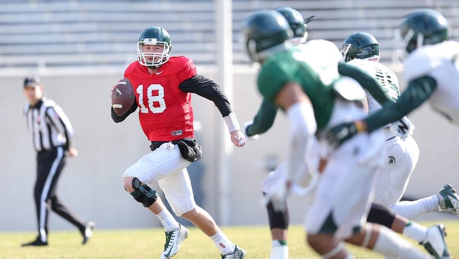 MSU senior quarterback Connor Cook escapes the rush during a scrimmage on April 10 at Spartan Stadium. Cook enters his third season as the Spartans' starting QB, a year with more preseason hype and accolades than ever before.