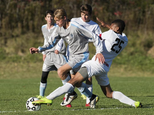 CVU's Trey Tomasi (25) battles for the ball with South Burlington's Ben Knudsen (2) during the high school boys soccer game between the South Burlington Rebels and the Champlain Valley Union Redhawks on Monday afternoon in Hinesburg.