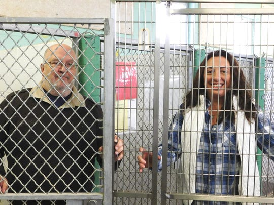 John Glass, left, and Kelly Askins display the indoor kennel doors. Glass who is retiring this week ordered the new doors like the one Askins is holding to allow people to see the dogs better in the kennels and with other improvements over the door he is holding.