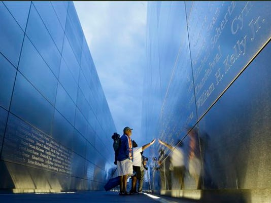 """Jimmie Corley and wife, Rosiland Corley look for the name of a family member on the """"Empty Sky"""" memorial to New Jersey's victims of the Sept. 11, 2001 terrorist attacks early Friday, Sept. 11, 2015, in Jersey City, N.J.  Victims' relatives began marking the 14th anniversary of Sept. 11 in a subdued gathering Friday at ground zero, with a moment of silence and somber reading of names. (AP Photo/Mel Evans)"""