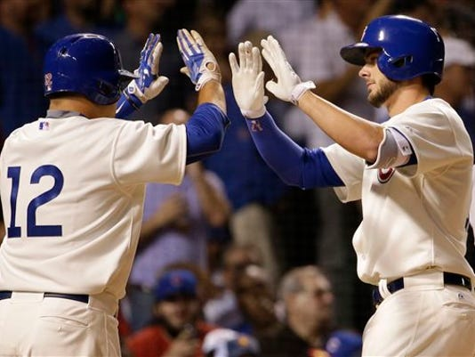Chicago Cubs' Kris Bryant, right, celebrates with Kyle Schwarber after hitting a two-run home run during the third inning of a baseball game against the Detroit Tigers, Wednesday, Aug. 19, 2015, in Chicago.
