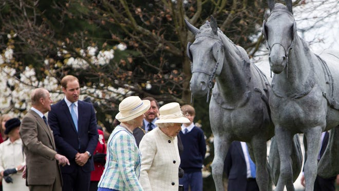 Britain's Queen Elizabeth II, Prince Philip, Duke of Edinburgh and Prince William, Duke of Cambridge walk past the unveiled Windsor Greys statue that marks 60 years of the Queen's Coronation at Windsor, Berkshire, on March 31, 2014. The life size sculpture depicts a pair of the Queen?s Windsor Greys which are two of the lead carriage horses used in state occasions.