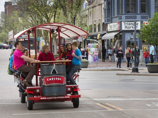 Party goers make their way down State Street in Madison, Wis., on a 14 passenger quadricycle.
