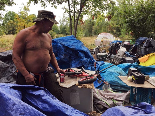 """Mohawk"" Craig Alexenko sits on top of refuse cleared out of a homeless encampment along the Springwater Corridor during a police sweep in southeast Portland."