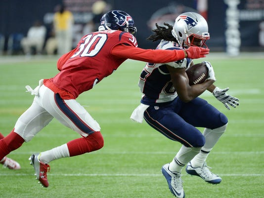 New England Patriots wide receiver Keshawn Martin (82) makes a catch in front of Houston Texans strong safety Kevin Johnson (30) during the first half of an NFL football game Sunday,  Dec. 13, 2015, in Houston. (AP Photo/George Bridges)