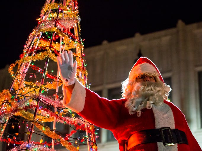 Santa Clause waves at spectators during the Rekindle