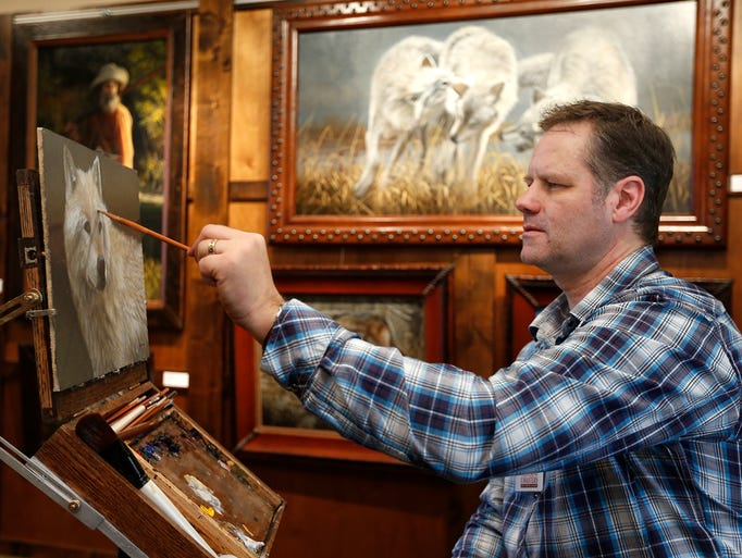 Joe Kronenberg of Spirit Lake, Idaho uses oil to paint a wolf in his Heritage Inn room at the Western Masters Art Show and Sale Wednesday.