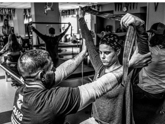Samantha and her father, Greg Schultz, doing adaptive yoga. Photo by Dr. Eric Spier