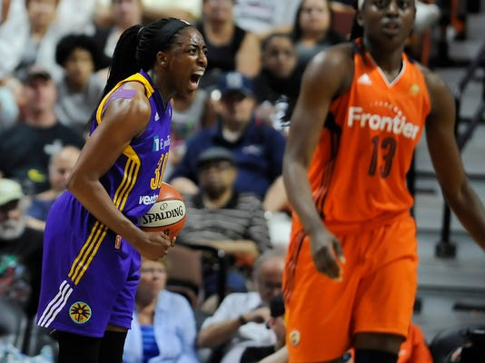 Los Angeles Sparks' Nneka Ogwumike, left, reacts after forcing sister and opponent Connecticut Sun's Chiney Ogwumike, right, into a shot clock violation during second half of a WNBA basketball game, Friday, July 15, 2016, in Uncasville, Conn. The Sparks won in overtime 98-92. (AP Photo/Jessica Hill)