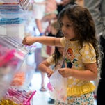 Five-Year-old Julia Fernandez selects some of her favorite candies from the display at Bubba's Sweet Spot in downtown Pensacola Friday morning. The long awaited candy store owned by PGA Golfer Bubba Watson, and Quint and Rishy Studer opened Friday morning July 1.