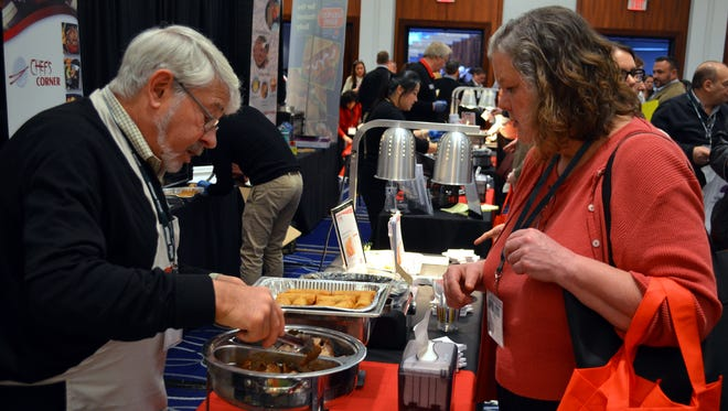 Marcia Brenneman, Washington Township, Morris County, School Food Service Director (right) samples an item at a vendor booth during the USDA Foods Conference in New Brunswick on Jan. 21.
