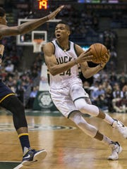 Milwaukee Bucks' Giannis Antetokounmpo puts a move on Indiana Pacers' Paul George during the first half of an NBA basketball game Wednesday in Milwaukee.