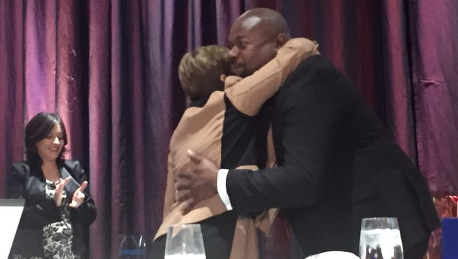 Joseph Searles, right, of Excellus BlueCross BlueShield hugs Ibero CEO Hilda Rosario Escher before accepting the Community Servicer Award on Thursday at the Riverside Convention Center.